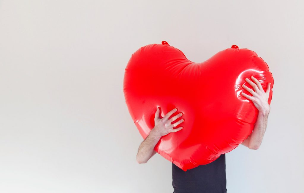 A person hugs a large red inflatable love heart. Health and love concept