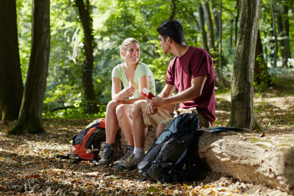 Couple Sitting on Trunk and Eating Hiking Snack After Trekking