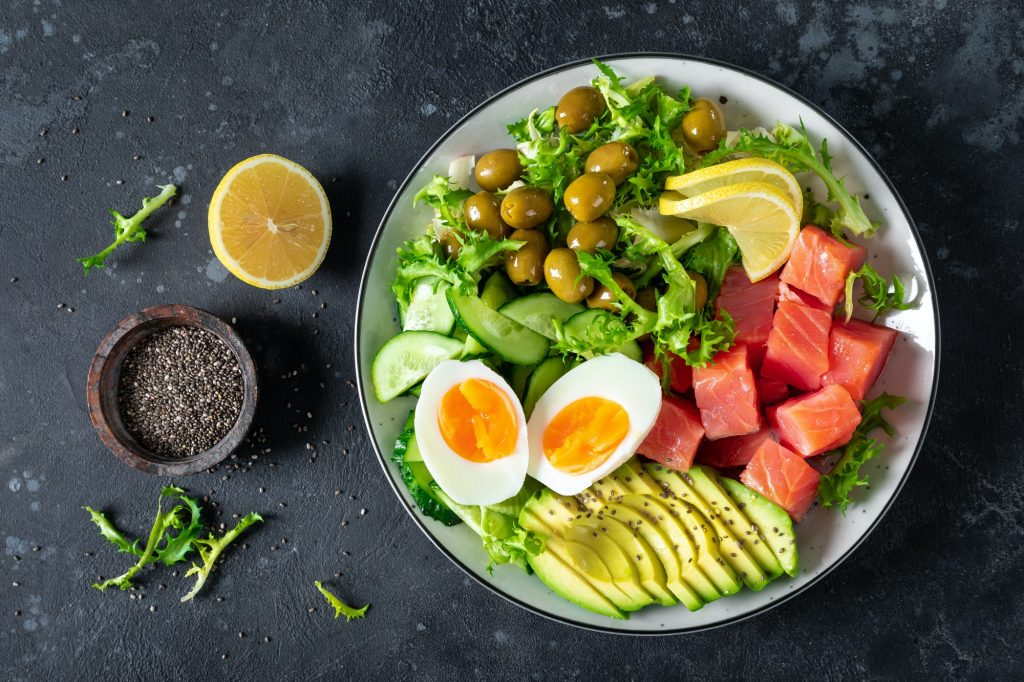 Ketogenic, paleo diet lunch bowl with salted salmon fish, lemon, avocado, olives
